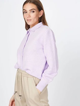 Woman poses side on wearing lilac collared long sleeve top and stone lounge trousers.