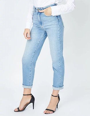 Close up of legs of woman posing wearing light wash denim mom jeans, white shirt and black slingback heeled sandals.