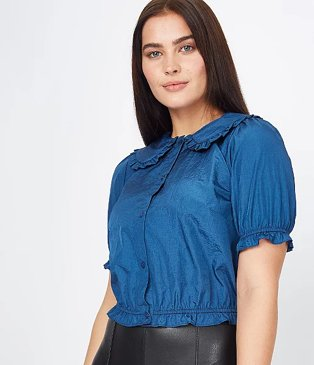 Woman poses wearing blue taffeta frill collar boxy blouse and black faux leather trousers.