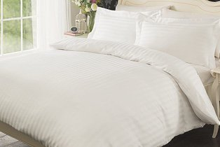 A double bed with white striped duvet set