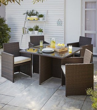 Outdoor area with the Jakarta 5 piece cube patio set with plates and drinks on it