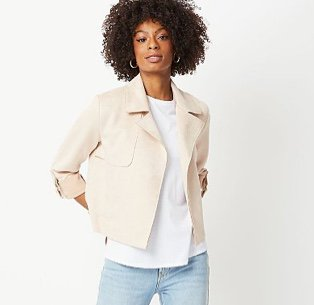Woman in a stone faux suede biker jacket over a white T-shirt and light jeans