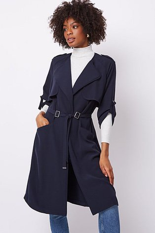 Woman in a navy belted longline trench coat over a white high neck jumper and jeans