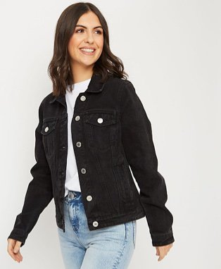Woman in a black denim jacket over a white T-shirt and jeans
