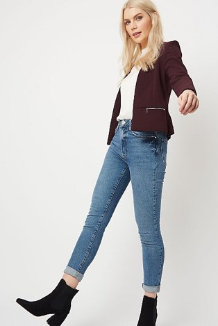 Woman in a purple formal textured zip detail blazer over a white jumper and jeans