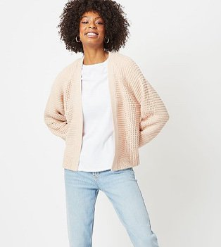 Woman in a pale pink ribbed waffle knit cardigan over a white top and light jeans
