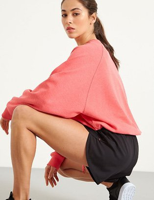 Woman crouching down in a pink sweatshirt and black sports shorts