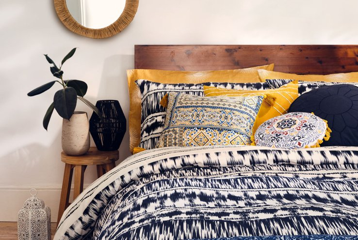 A close shot of a double bed with an animal print duvet set and a selection of animal print and geometric cushions.