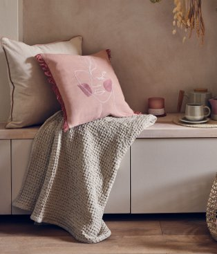A seating bench topped with cream and pink cushions, a neutral throw and a selection of speckled crockery.