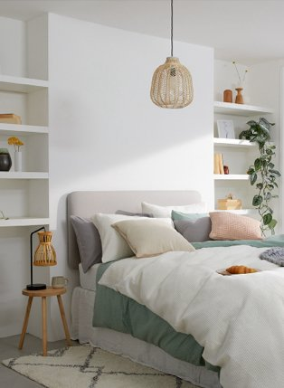 A double bed topped with a selection of bedding in white, green, grey and orange, a bedside table with a wicker lamp and a variety of picture frames, planters and vases on built-in shelves.