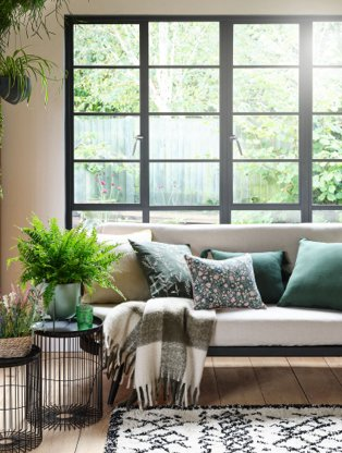 A sofa topped with a selection of green cushions and throws next to side tables with plants and vases, all in front of a bright window.