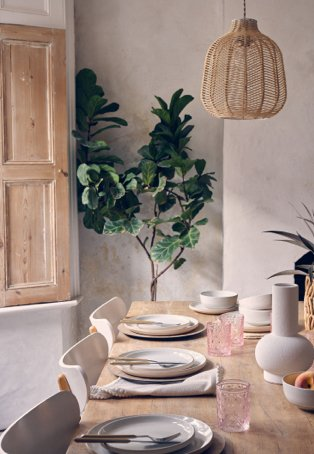 A wooden dining table topped with speckled crockery, pink glasses and neutral cutlery in a rustic dining room with wooden cupboards and planters.