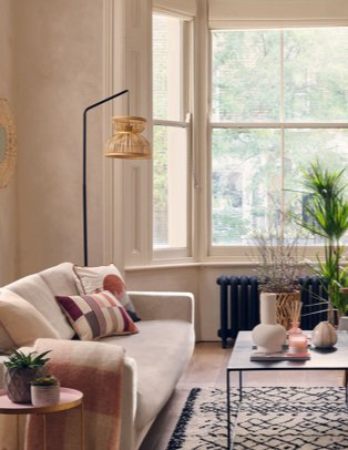 A pale sofa topped with cream, pink and burgundy patterned cushions and throws in a living room with wicker lamps, planters, vases and a selection of candles and decorative items.