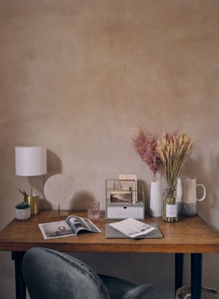 A wooden desk topped with magazines, a white lamp, gold storage pots and a variety of vases and planters.