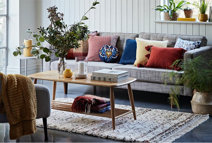 A grey sofa with a selection of different coloured cushions on top, behind a wooden coffee table topped with books, two candles and a vase full of flowers