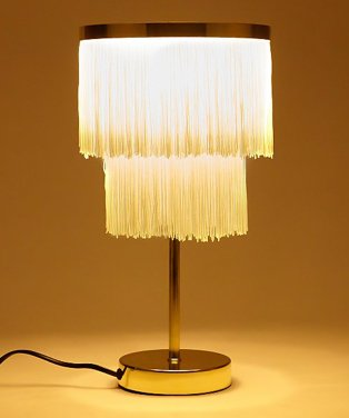 A lit up gold tone fringe table lamp