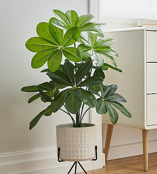 An artifical plant in a white planter on a black metal stand