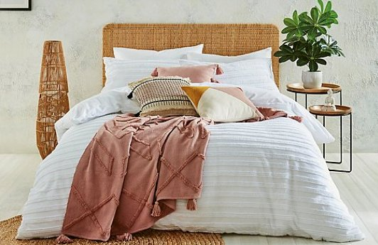 A double bed with a white striped duvet set, a selection of pink, white and stone accent cushions and a pink throw