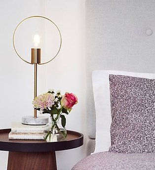 A bed with a purple duvet set next to a wooden bedside table, topped with a gold hoop table lamp and small vase of flowers