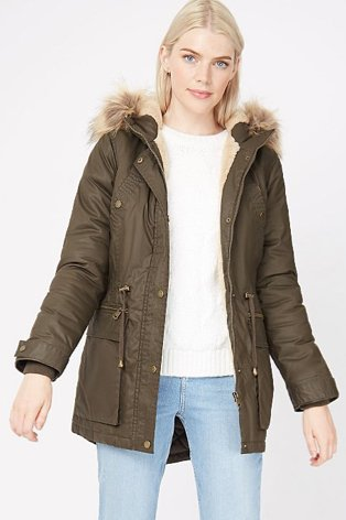 A woman wearing light wash jeans, a cream jumper and a khaki parka with faux fur trim