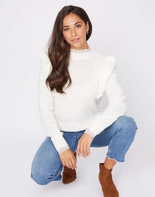 A woman crouching wearing blue jeans with frayed edges, brown boots and a cream ribbed lace collar ruffle jumper