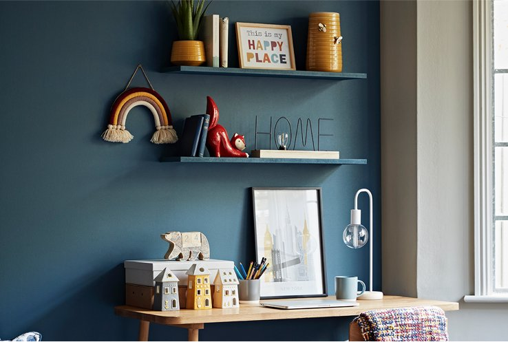 Two wall shelves topped with an assortment of books, planters & vases, fox ornaments and slogan signs above a wooden desk with a lamp, laptop and framed skyline print