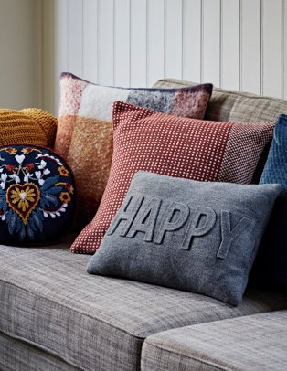 A grey sofa with a yellow knitted throw over one arm and a selection of blue, red and yellow cushions on top