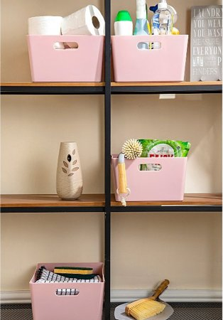Pink storage boxes on wooden shelves filled with cleaning products, toilet rolls and towels