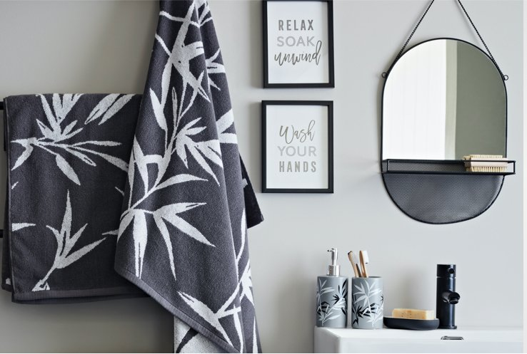 A bathroom with black and white printed towels on a black ladder, a white sink with black fixtures and black and white tumblers, and an oval mirror and black photo frames on the wall