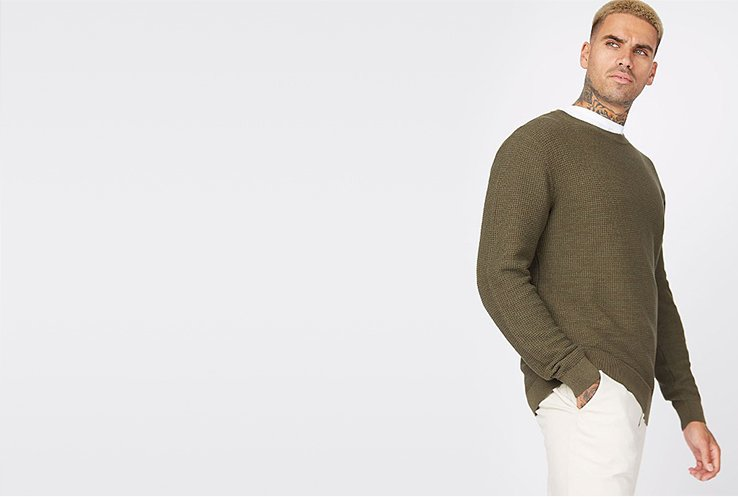 Man wearing cream trousers with a white t-shirt and khaki waffle textured knit jumper