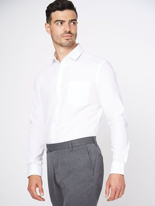 Man wearing grey formal trousers with a white long sleeved shirt