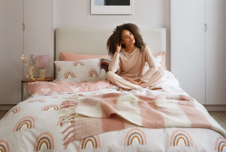 Woman sits on bed with cream rainbow printed bedding topped with pink and cream plaid throw wearing light pink loungewear.