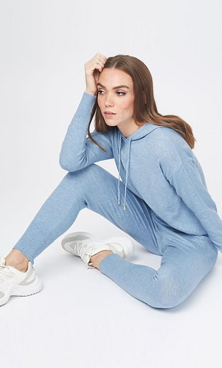 Woman sits on floor posing wearing coordinating pale blue knitted hoodie, skinny joggers and white trainers.