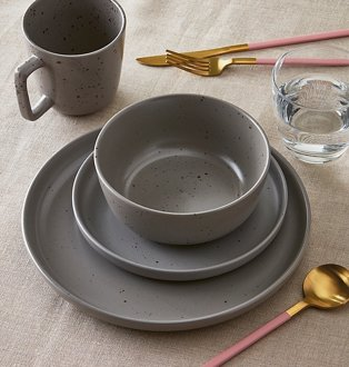 Stack of speckled grey plate, side plate and bowl next to matching mug, clear tumbler and pink and gold-tone cutlery.