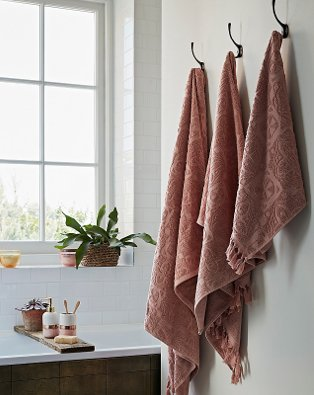 White bathroom with pink textured towels hanging from silver hooks