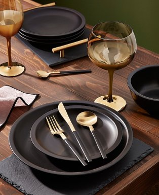Wooden table with matte black tableware, amber bubble gin glasses and black and gold-tone cutlery.