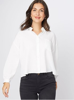 A woman wearing a white blouse with black trousers