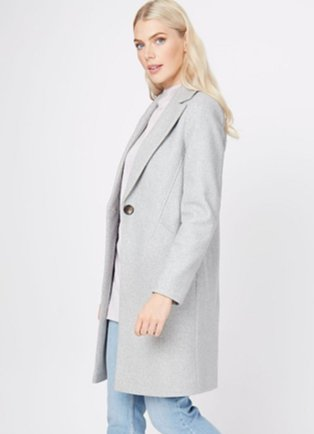 A woman wearing light wash jeans, a white top and a grey marl longline formal coat