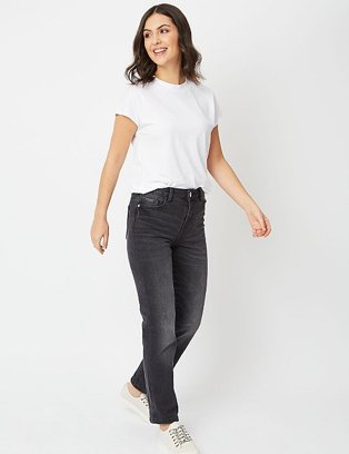 A woman wearing black wash denim high rise jeans with a white t-shirt and white trainers