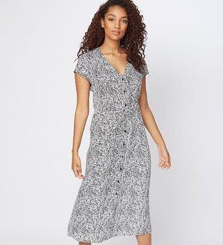 A woman wearing a white abstract animal print midi shirt dress