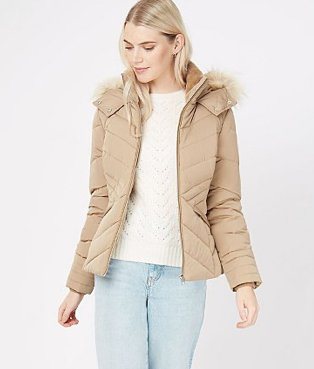 A woman wearing light wash jeans, a white jumper and a stone faux fur collar padded jacket