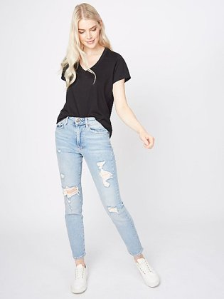 Woman wearing a black V-neck t-shirt and light blue ripped jeans