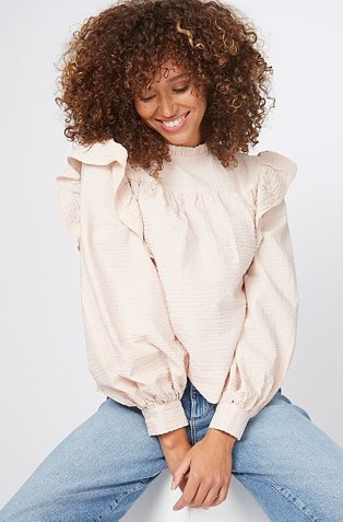 Woman wearing a white puff sleeve jumper with light blue jeans