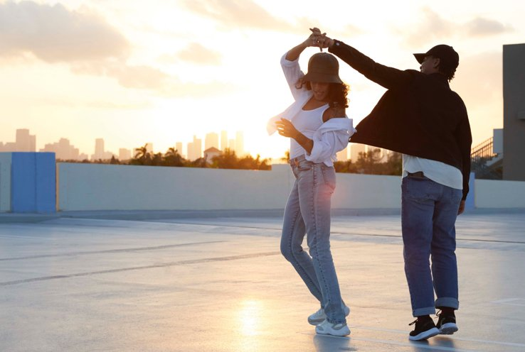 Man and woman dancing on top of a building with sun setting in the background.