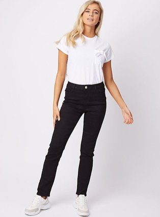Blonde woman posing wearing white crew neck t-shirt, black jeans and white trainers.