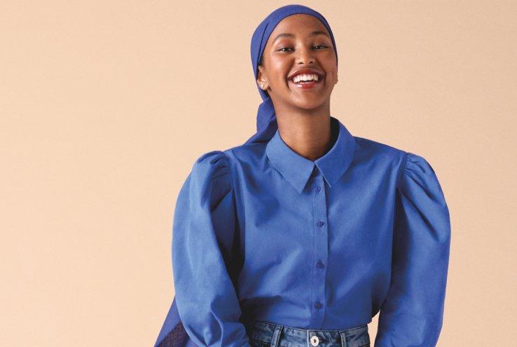 Woman smiles wearing cobalt blue poplin puff sleeve shirt with head scarf.
