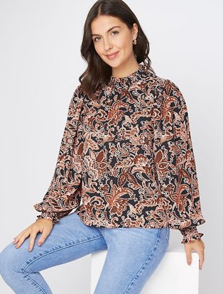 Brunette woman sits on white box wearing burnt orange paisley print high neck blouse and light blue jeans.