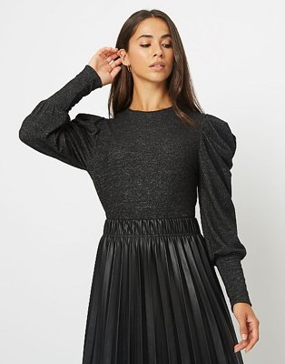 Brunette woman poses raising left hand to face wearing black pleated sleeve jumper and black PU pleated skirt.
