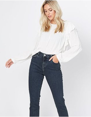 Blonde woman poses wearing white textured high neck frill detail blouse and dark blue jeans.