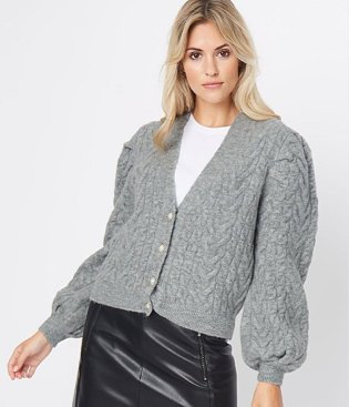 Blonde woman poses wearing white crew t-shirt, grey cable knit balloon sleeve cropped cardigan, black PU mini skirt and tights.